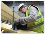 03 Local skilled workers measure and cut the timber beams for the roof over the entrance hall on the College side