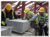 15 Michael Cregg, Gary Cregg and Christopher Donnegan move the coping stone into place on top of fresh mortar