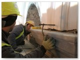 19 Workers make sure that the top of a side wall pilaster is level